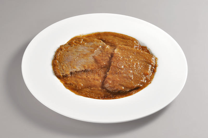 Dish with portion of braised meat stock image