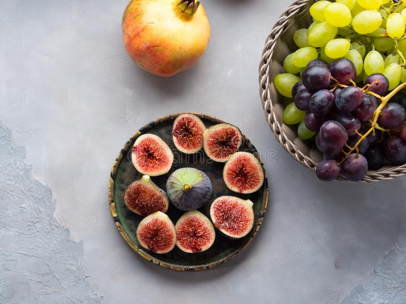 Dish of purple figs, grapes and pomegranate. Dish of purple italian figs, basket of grapes and pomegranate on gray background. Autumn winter fruit snack still stock images