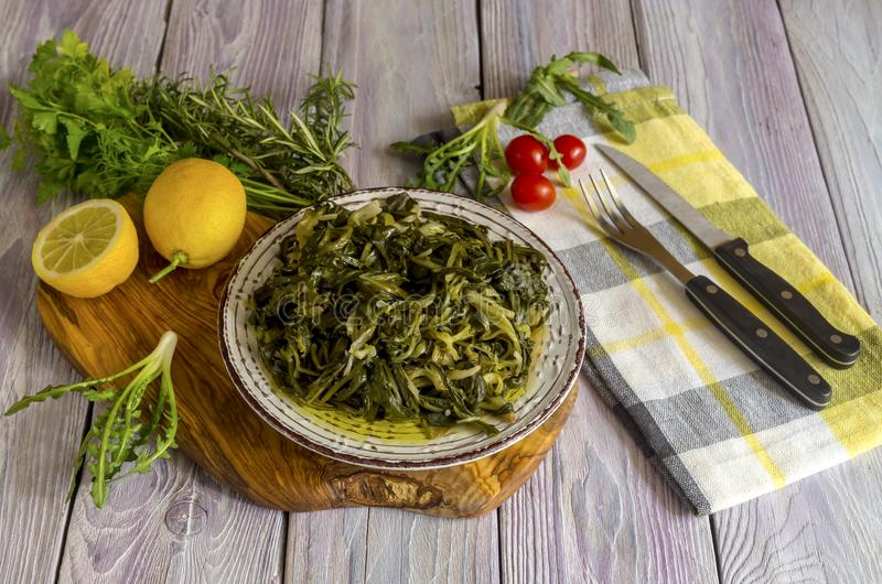 A dish of rare boiled grass `stamnagathi`Cichorium spinosum. Cretan cuisine. A dish of rare, wild, useful boiled grass `stamnagathi` Cichorium spinosum, that stock image