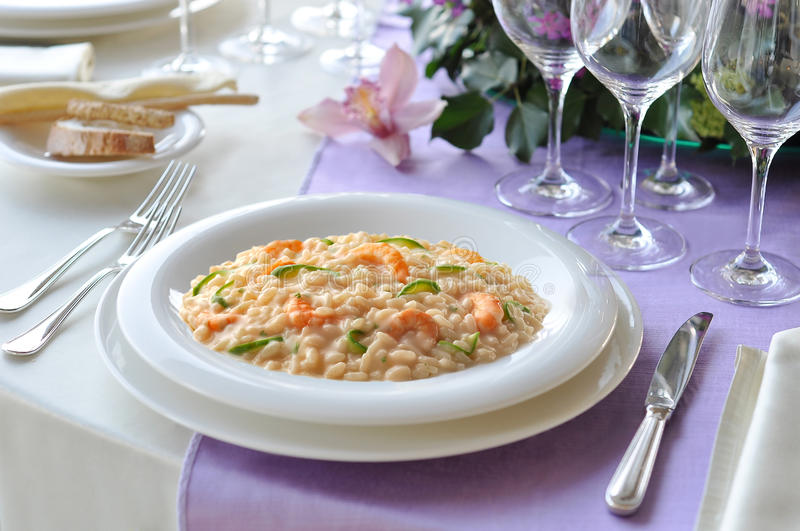 Dish of Risotto with Prawns and Zucchini. On laid table royalty free stock photography