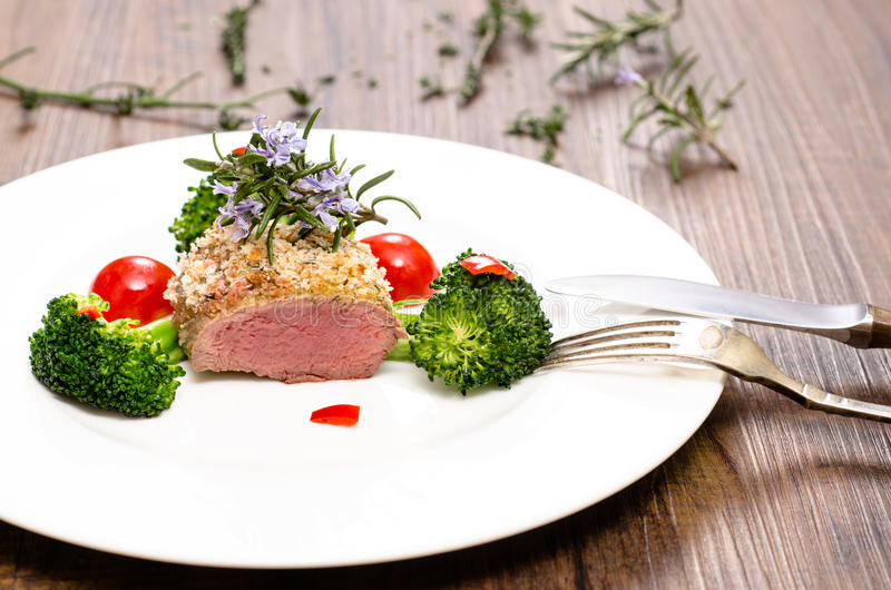 Dish with saddle of lamb. Broccoli, tomatoes and chili royalty free stock photography