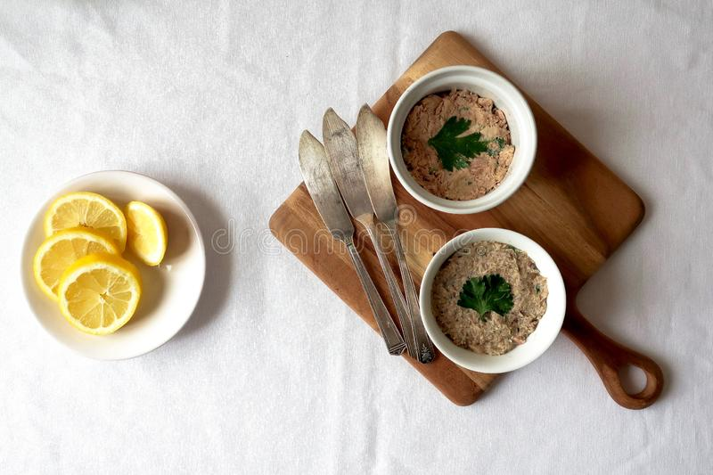 A dish of sliced lemons beside two ramekins of Seafood Rillettes royalty free stock photo