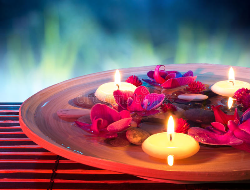 Dish spa with floating candles, orchid, in garden royalty free stock photo