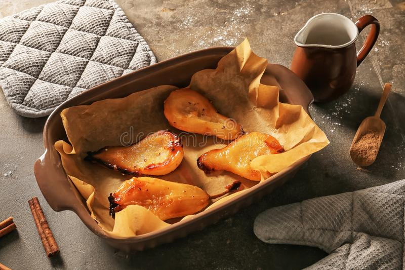 Dish with tasty baked pears on grey table royalty free stock photo