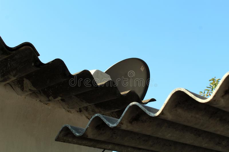 Dish tv antenna mounted on Home roof. Picture of a dish tv antenna mounted on home roof in village area of india. Now almost every home had a dish connection on royalty free stock photo