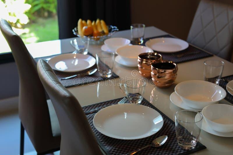 Dish ware se organiza na mesa do café da manhã, dentro da sala de jantar da casa moderna foto de stock royalty free