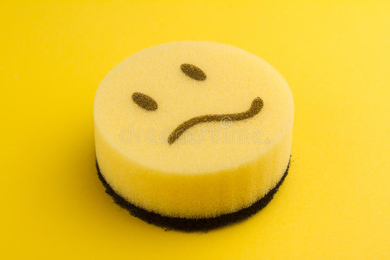 Dish washing concept with yellow sponge. Dish washing concept yellow sponge with sad scared face royalty free stock images