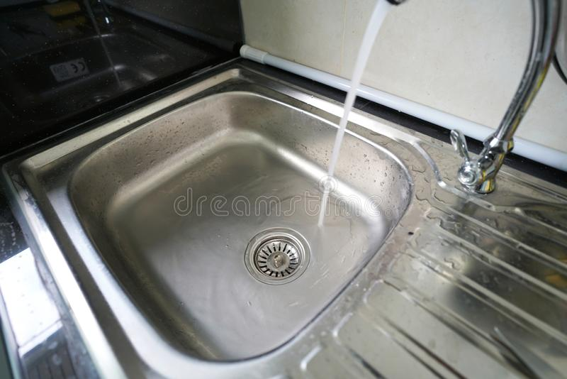 Dish washing sink and water flow royalty free stock photography