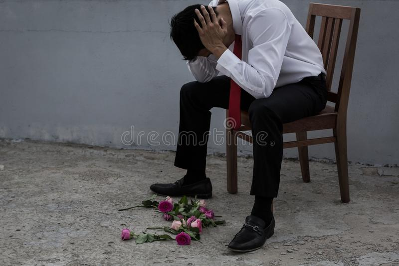 A disheartened man in a suit, broken-hearted after being rejected. Asian man looks heartbroken because his date cancelled. He looks at the flower bouquet that he stock photography