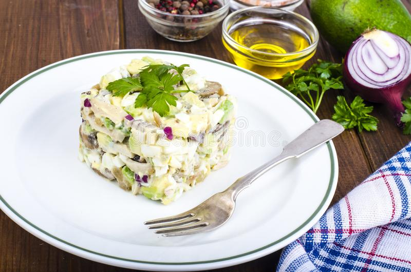 Dishes with avocado, salad with mushrooms and eggs, mayonnaise sauce royalty free stock image