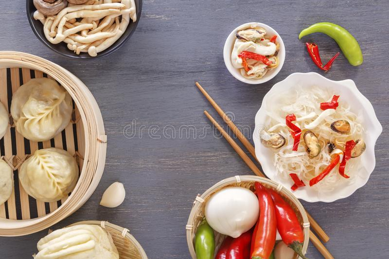 Dishes of Chinese cuisine in assortment. Steam dumplings, noodles, salads, vegetables, mushrooms, seafood. Top view. Copy space stock photo