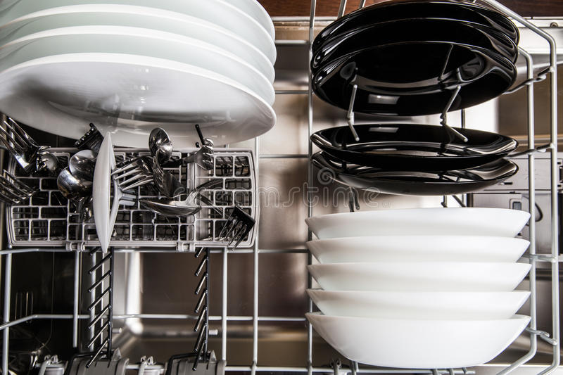 Dishes after cleaning in dishwasher machine stock image