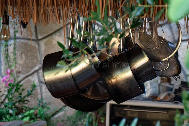 Dishes hang in a cafe. Storage and drying. Outdoor cafe kitchen on a sunny day, summer. Dishes hang in a cafe. Storage and drying. Outdoor cafe kitchen on a stock photos