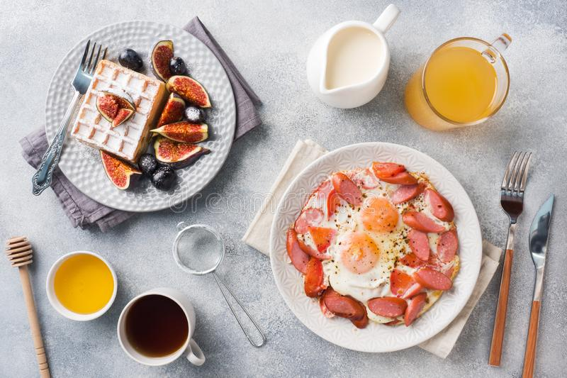 Dishes for home cooked hearty Breakfast. Fried eggs with sausages and tomatoes. Belgian fluted waffles with figs and grapes. Gray. Concrete background stock photography