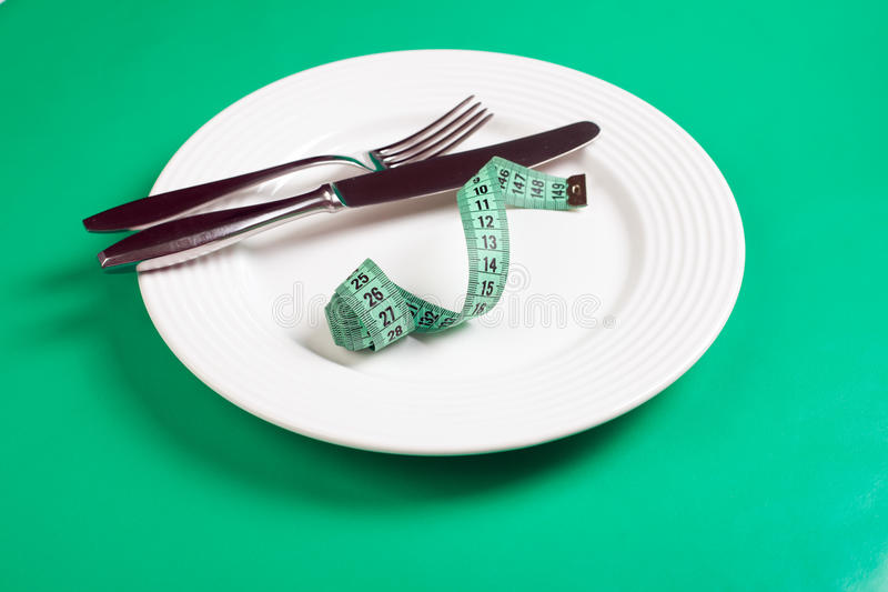 Dishes with measuring tape. On green background royalty free stock photography