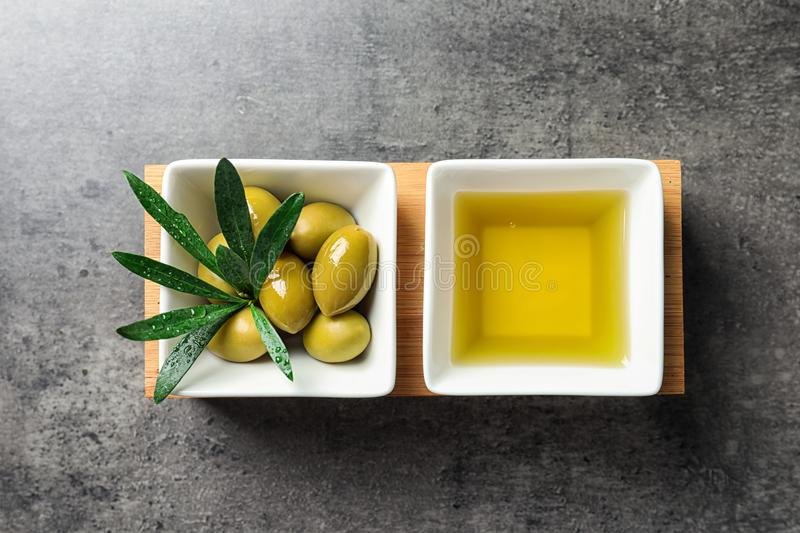 Dishes with olive oil and ripe olives on table royalty free stock photos