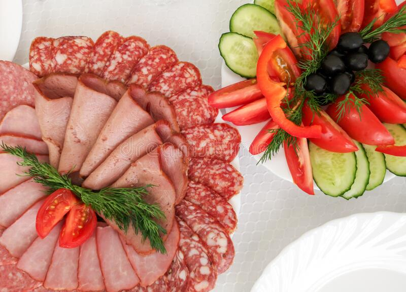 Dishes and salads of sausage and tomatoes stock image