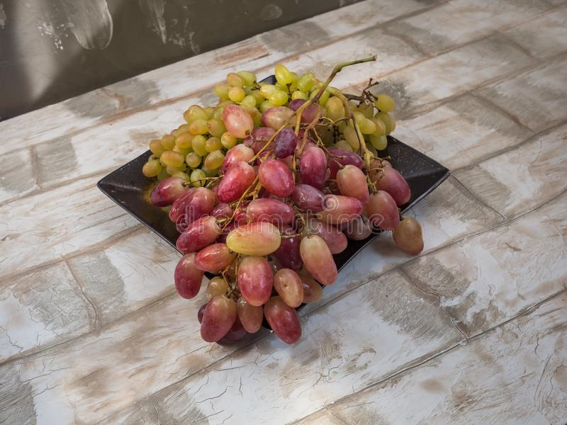 Dishes from white grapes close-up on a ceramic plate stock photography