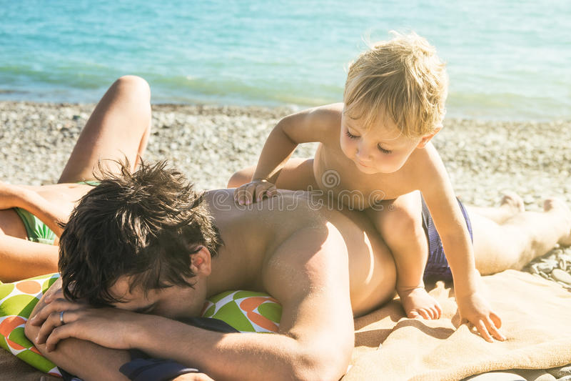Disheveled疲倦了爸爸不要使用与海滩的婴孩 库存图片