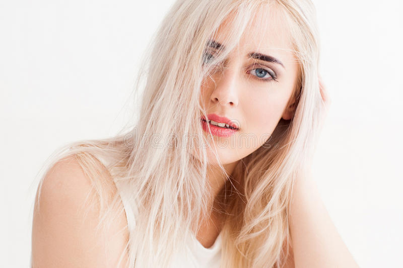 Disheveled blonde calmly and trustingly looks. Confident blonde with big blue eyes, bright eyebrows. Her long white hair disheveled, she calmly and trustingly royalty free stock images