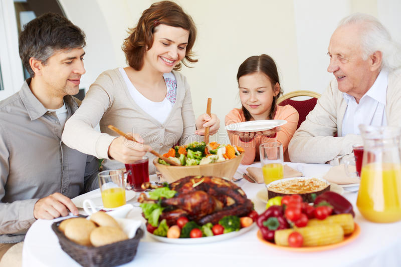 Dishing salad. Mother putting salad on plate of daughter royalty free stock image