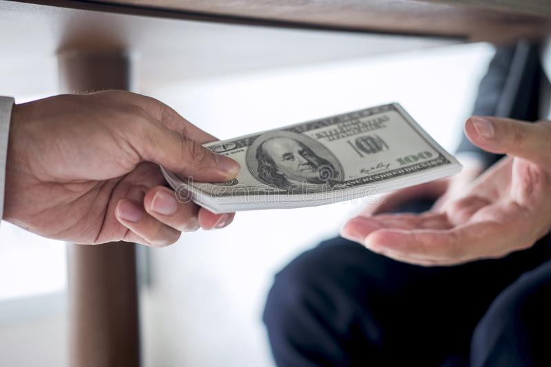 Dishonest cheating in business illegal money, Businessman receive bribe money under table to business people to give success the. Deal contract of investment stock images