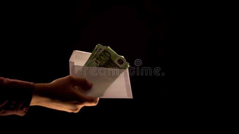 Dishonest man taking envelope with euros banknotes, black background, corruption royalty free stock image