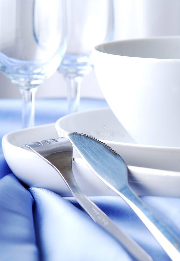 Dishware на голубой скатерти стоковые изображения