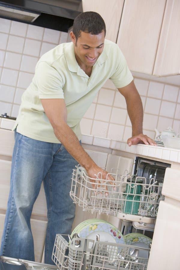 dishwasher loading man στοκ εικόνες
