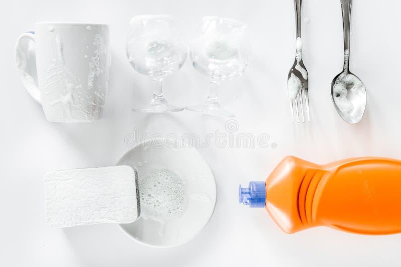 Dishwashing vloeistof, spons en vaatwerk op witte hoogste mening als achtergrond stock fotografie