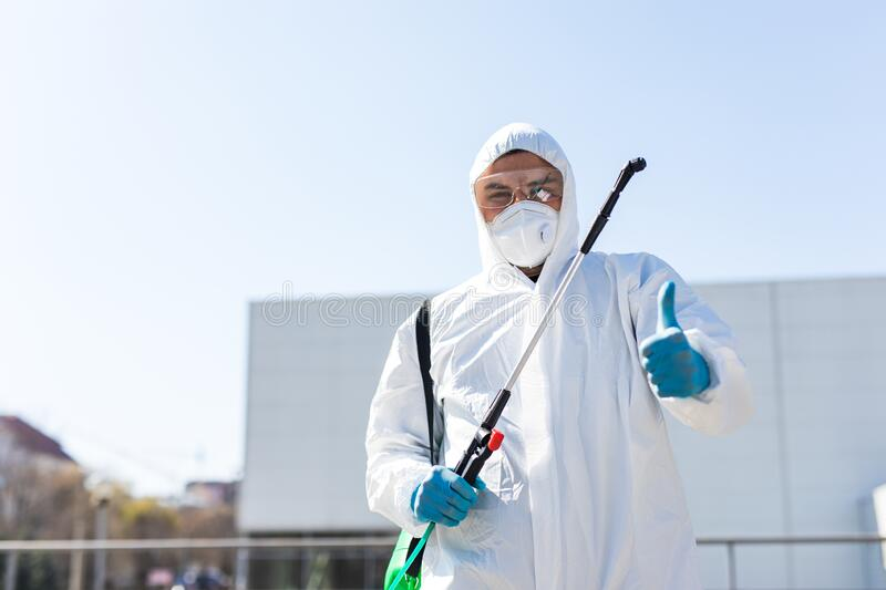 World pandemic. Disinfector in a protective suit and mask, holding disinfection chemicals outdoors stock photo