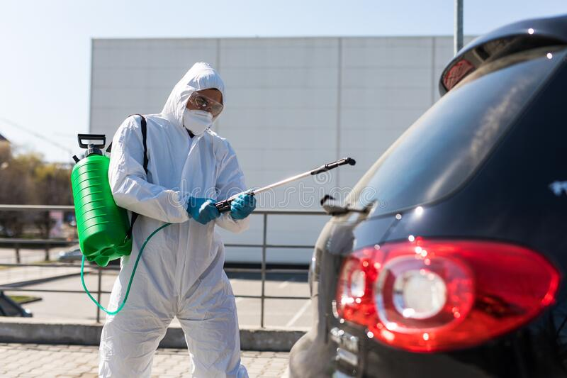 Coronavirus Pandemic. Disinfector in a protective suit and mask sprays disinfectants of car outdoors royalty free stock photography