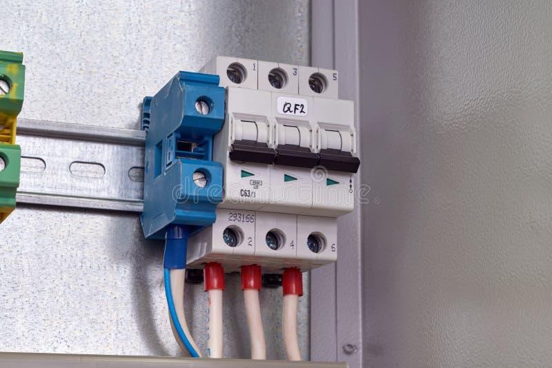 Disjoncteur modulaire et bornes de passage dans une armoire électrique photos stock