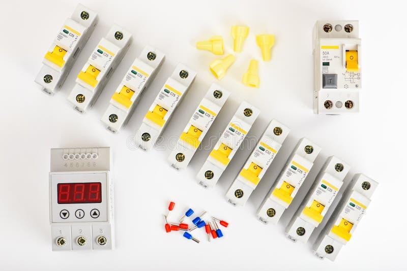 Disjoncteurs automatiques, bo?te de distribution, c?ble et multim?tre num?rique sur un fond blanc Appareillage ?lectrique photo stock