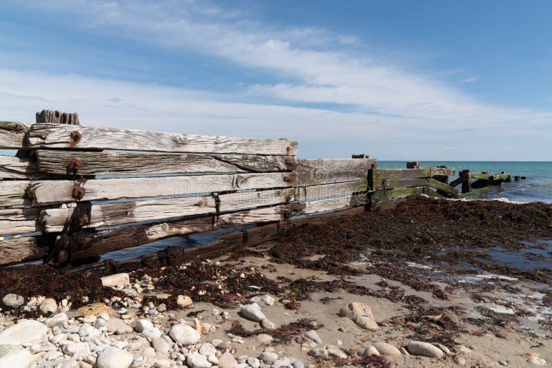 Disjuntores de onda de madeira velhos e resistidos na costa de mar da praia no verão imagem de stock