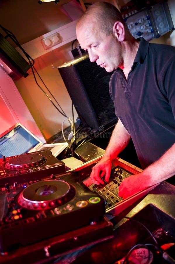 Disk Jockey. Older male as Disk jockey behind the mixing panel stock photos