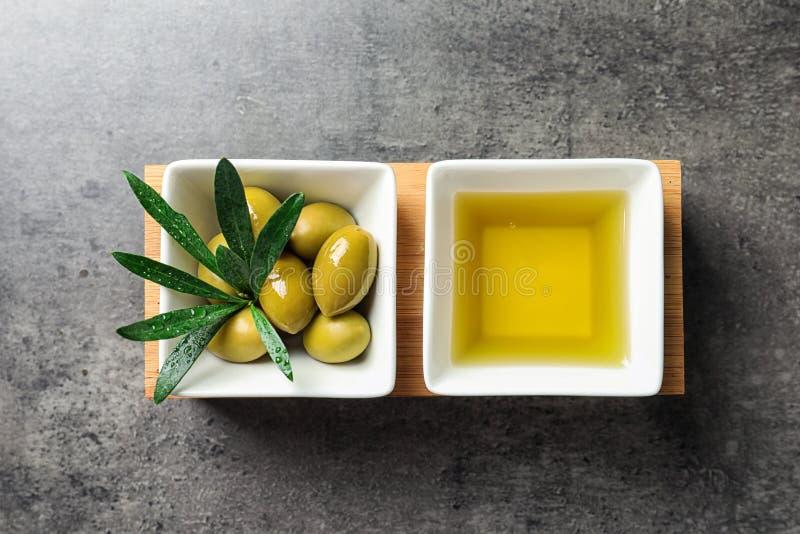Disk med olivolja och mogna oliv på tabellen royaltyfria foton
