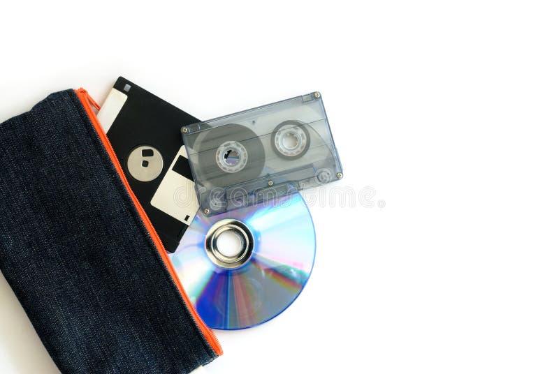 Diskette, audiobandcassette en compact disc in zak stock afbeelding