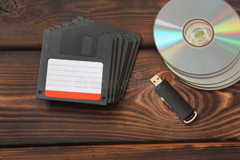 Disketter, USB pråligt drev och skivor på en träbakgrund arkivfoton