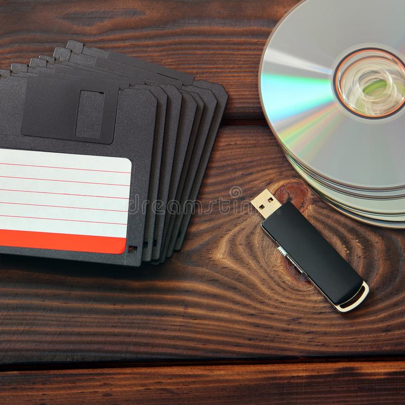 Disketter, USB pråligt drev och skivor på en träbakgrund royaltyfri fotografi