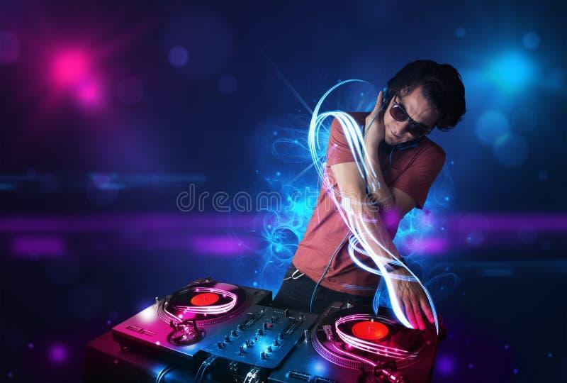 Diskjockey, der Musik mit elektrischen Lichteffekten und Lichtern spielt stockbild