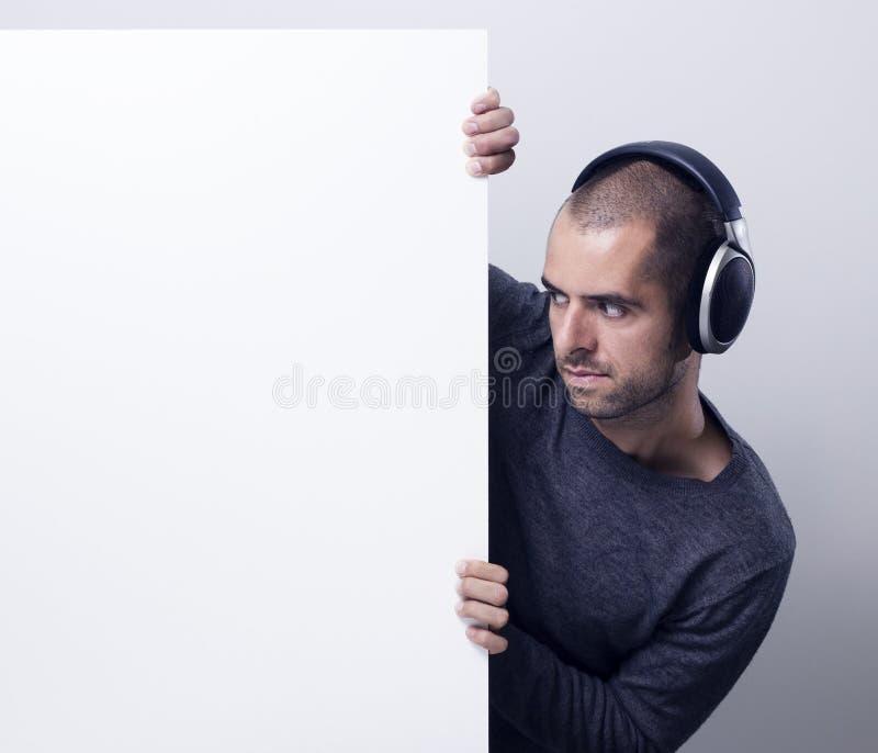Diskjockey som rymmer en vit affischtavla royaltyfri fotografi