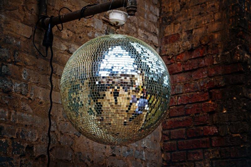 Diskospegelboll framme av en gammal tegelstenvägg på en grungy del arkivfoto