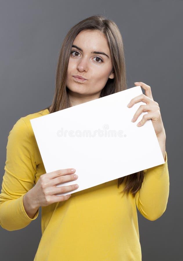 Diskret 20-talflicka som gör en annonsering, i att visa ett tomt mellanlägg framme av henne arkivfoton