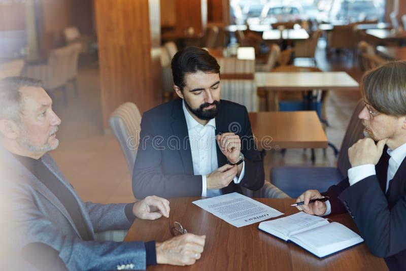 Diskussion des Geschäfts-Vertrages im Café lizenzfreie stockfotos