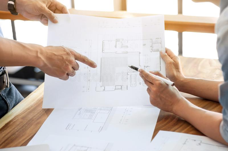 Diskussion för två teknikerer på arkitektoniskt projekt på konstruktionsplatsen på det moderna kontoret arkivfoton