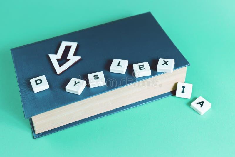 Dislexia e palavras lidas com um livro aberto fotografia de stock