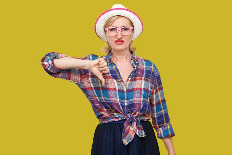 Dislike. Portrait of sad dissatisfied modern stylish mature woman in casual style with hat and eyeglasses standing looking at. Camera with thumb down. indoor stock image