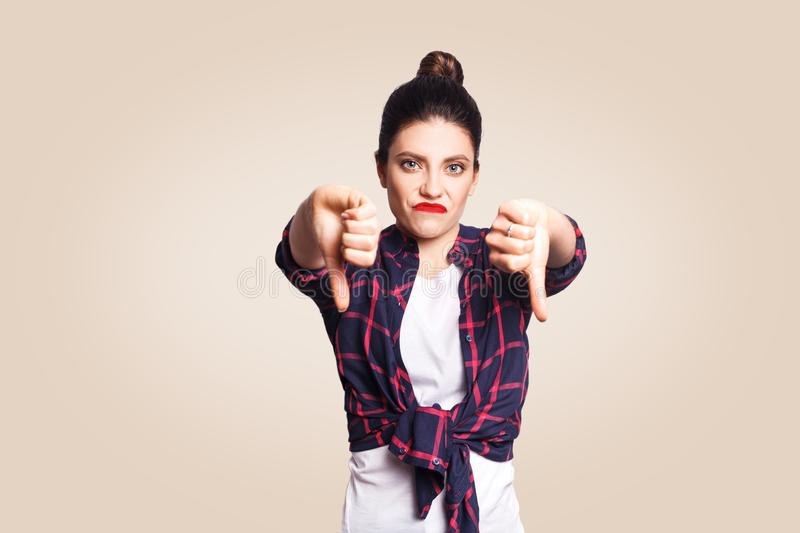Dislike. Young unhappy upset girl with casual style and bun hair thumbs down her finger, on beige blank wall with copy space looki. Ng at camera with toothy royalty free stock image