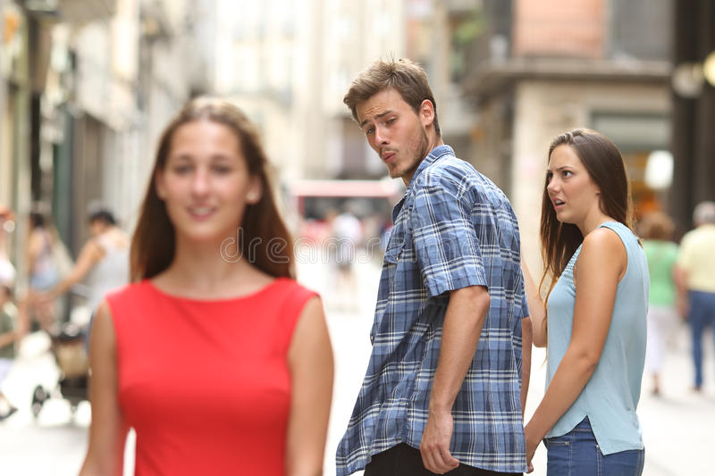Disloyal man with his girlfriend looking at another girl royalty free stock photo